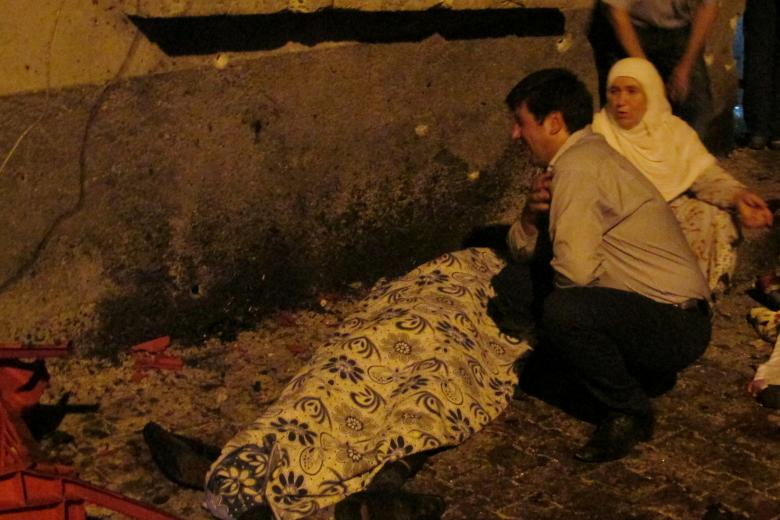 A man and a woman mourn next to a body of one the victims of a blast targeting a wedding ceremony in the southern Turkish city of Gaziantep, Turkey, August 20, 2016. Ihlas News Agency via REUTERS